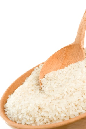 groat: rice grain in wooden spoon isolated on white background