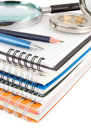 pen and pencil at pile of notebook isolated on white background photo