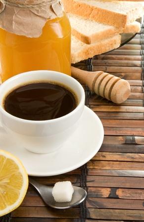 coffee, honey, lemon and bread on straw table photo