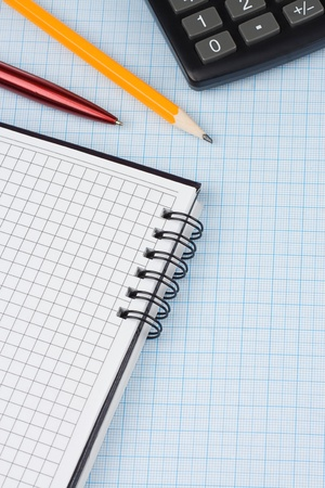 school accessories, dollars and checked notebook on graph grid paper photo