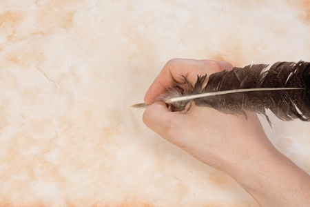 writing hand with feather at paper  photo