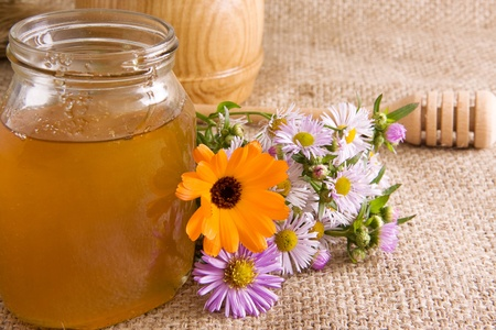 honeycomb, flowers and honey in glass on sacking photo