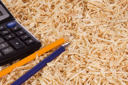 calculator and pencil at wooden shaving photo
