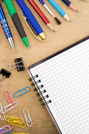school accessories and checked notebook on wooden texture Stock Photo - 12042055
