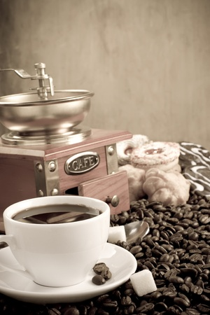cup full of coffee, beans, pot and grinder on wooden background photo