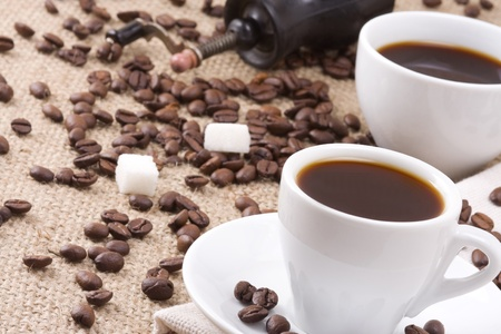 cups of coffee, beans and grinder on sacking photo