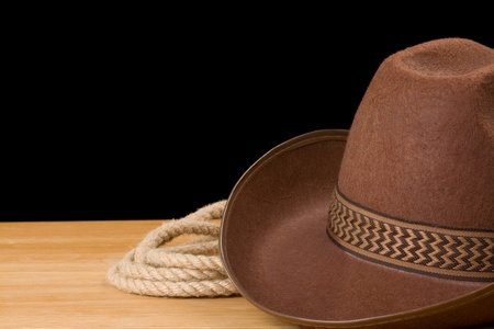 western attire: brown cowboy hat and rope isolated on black background Stock Photo