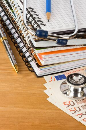 medical stethoscope with notebook and moneywood photo