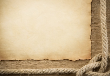 ship ropes and old paper on wood background photo