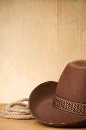 western attire: brown cowboy hat and rope on wood background
