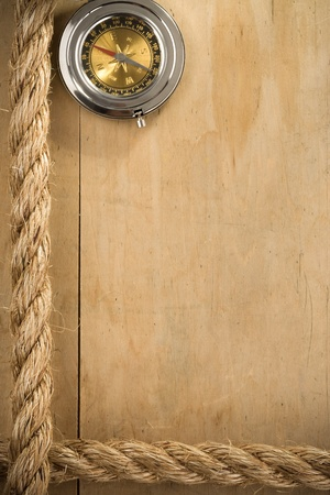 lashing: ship ropes and compass on wood background texture Stock Photo