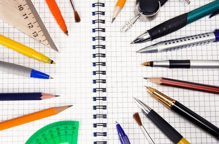 pens and pencils on checked notebook photo
