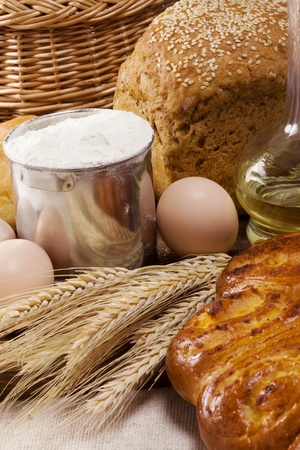 grain and cereal products: bread, oil, basket and eggs on sacking