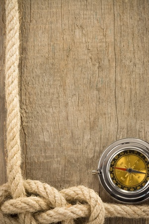 ship ropes and compass on wooden background texture photo
