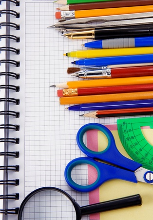 pens, pencils, magnifying glass and other office accessories on cheked notebook photo