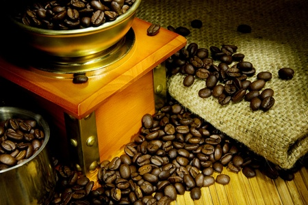 coffee grinder, beans and pot on sacking photo