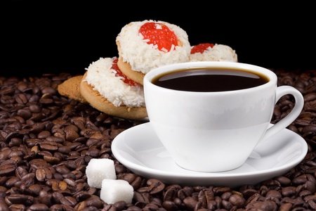 cup of coffee and cookies on beans photo