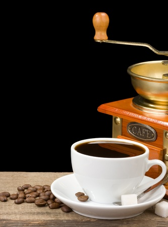 cup of coffee and grinder on beans photo