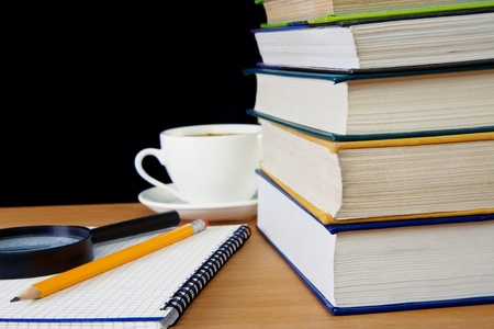 pile of books, pencil on notebook and cup of coffee on table photo