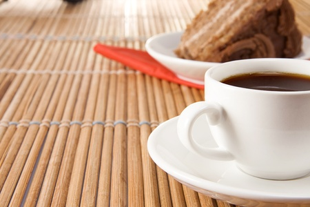 cup of coffee and sweet pie on wood straw table photo