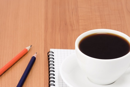 cup of coffee and pens with notepad on table photo
