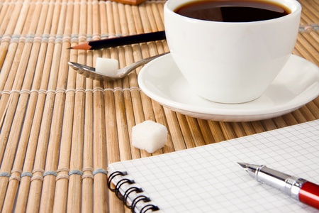 cup of coffee and pen with notebook on table photo