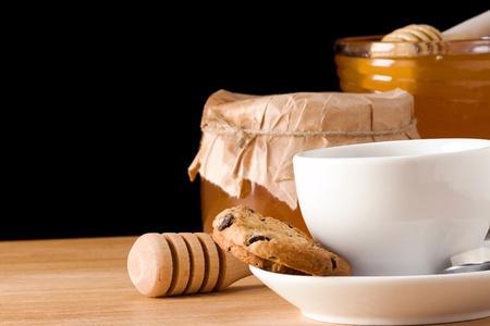 coffee, honey and cookies on black photo