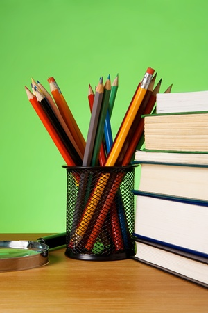 pile of books, magnifier and holder basket with colored pencils on green background photo