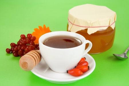 viburnum, berry dog, tea and honey on green photo