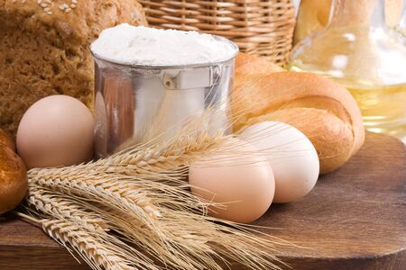 bread, oil, basket and eggs on board photo