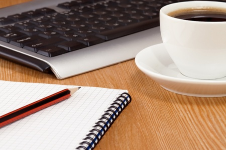 keyboard, notebook and cup of coffee on table photo
