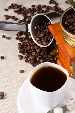 beans, cup of coffee and grinder on sacking photo