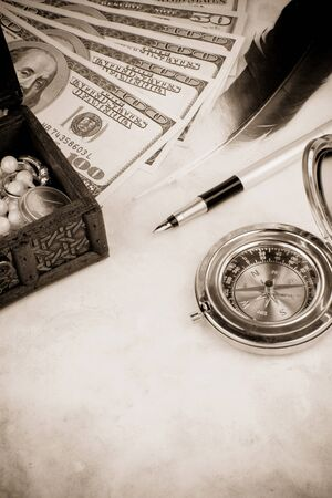 dollar, pen and feather at table on sepia photo