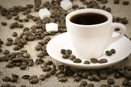 cup of coffee, beans on sacking material photo