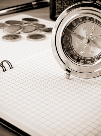 white and black image of compass, pen and coin photo