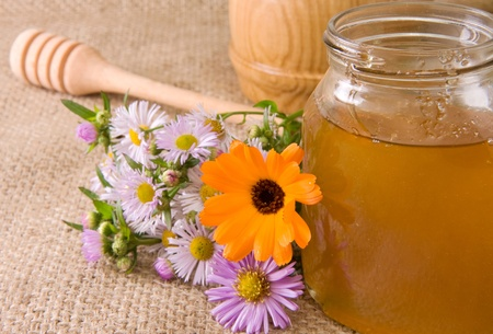 flowers and honey in glass pot on sacking photo