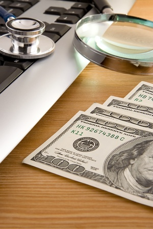 stethoscope at keyboard and dollars on wood photo