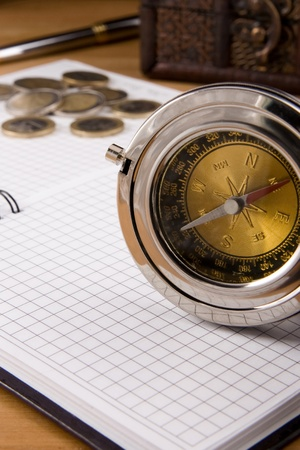 compass, pen and coin on checked notebook photo