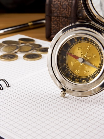 compass, gold coin and pen on checked notebook photo