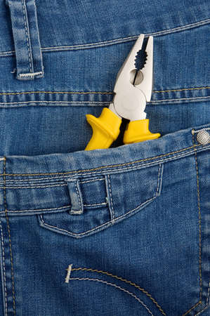 yellow pliers in pocket jeans photo