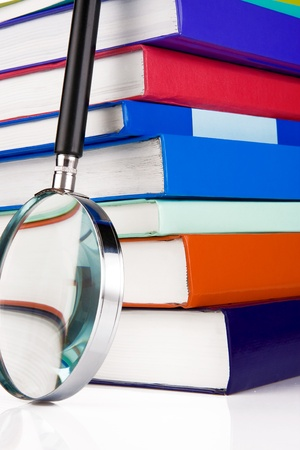 pile of books and magnifying glass isolated on white background photo