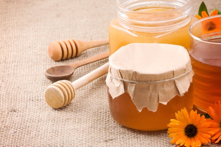 honey, flowers and honey in glass pot on sacking photo