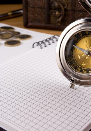 silver compass, gold coin and notebook photo