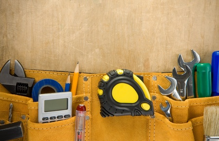 work belt: tools in construction belt on wooden texture