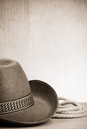 western attire: vintage brown cowboy hat and rope at wood background on sepia