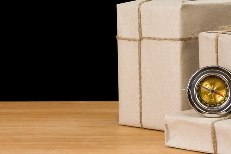 parcel wrapped and compass isolated on black  background photo