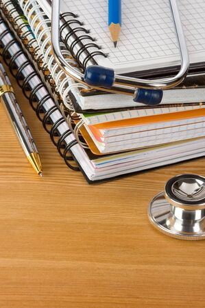 medical stethoscope with notebook at wood table background photo