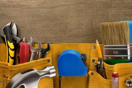 outils dans la ceinture de la construction sur la texture de fond en bois