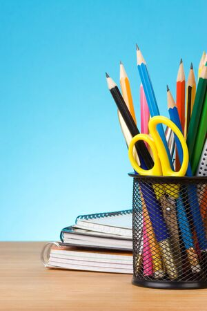 pen holder: back to school concept on blue background at wood