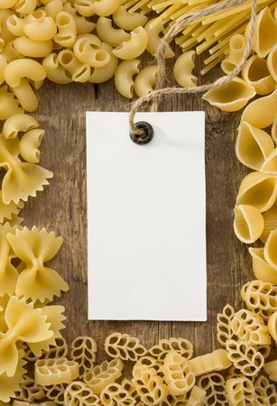 raw pasta and price tag on wood as background photo